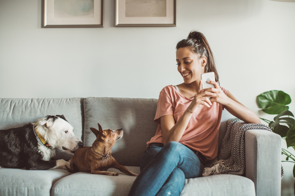 Young woman sitting on a couch with 2 dogs smiling at them